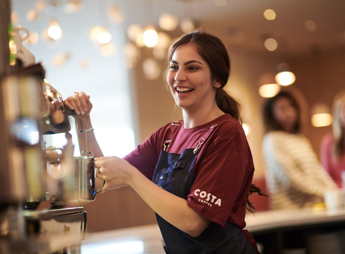 Costa Coffee Barista Frau an Maschine
