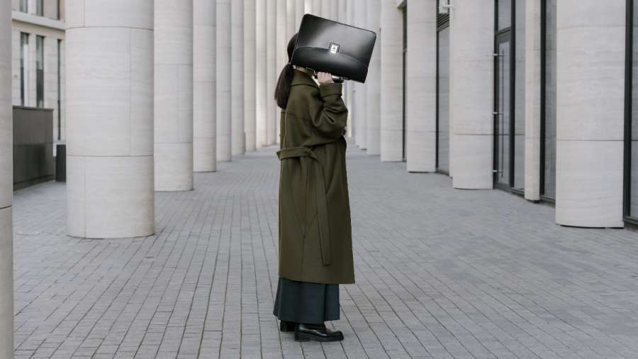Person in business professional clothes holding up a briefcase, covering their face. They're standing on concrete, surrounded by concrete pillars.
