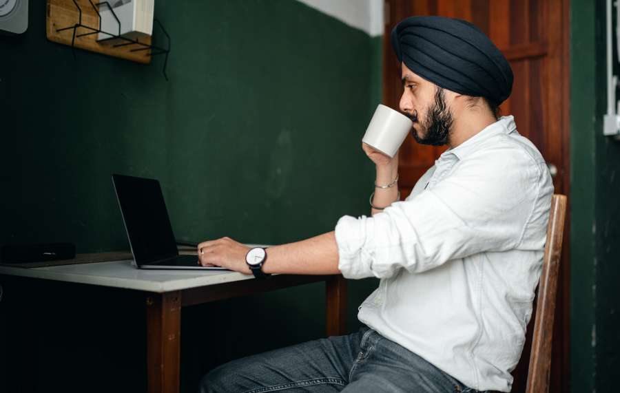 Man sipping coffee in front of laptop on desk