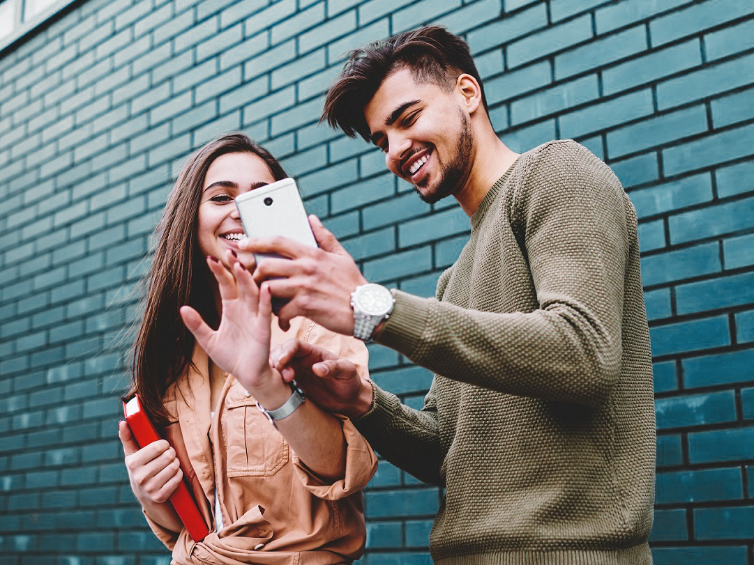 A young man and young woman smile while viewing a smartphone screen