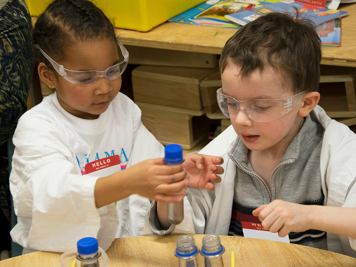 A pair of Scientists in School participants examining test tubes in their classroom