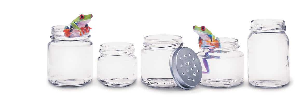Two tree frogs crawl on the openings of open jars