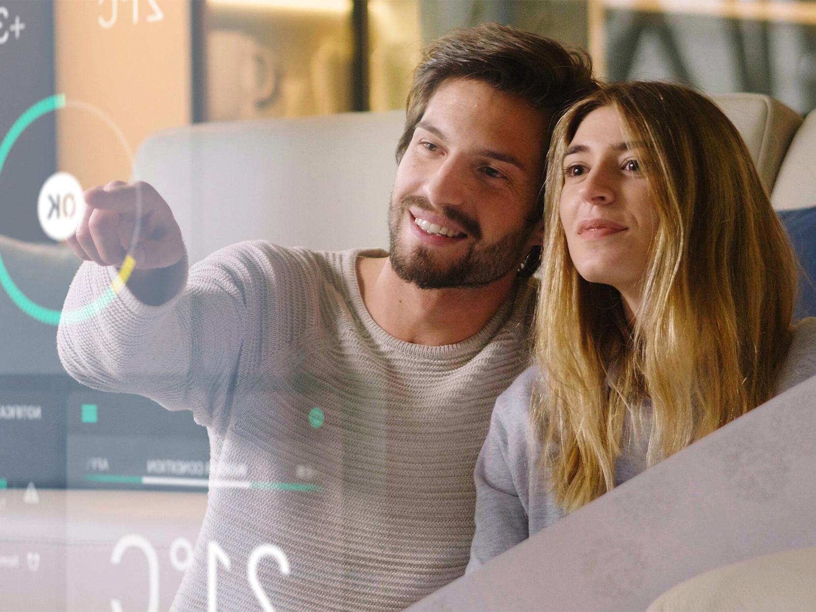 Une femme et un homme souriants pointant un grand écran transparent