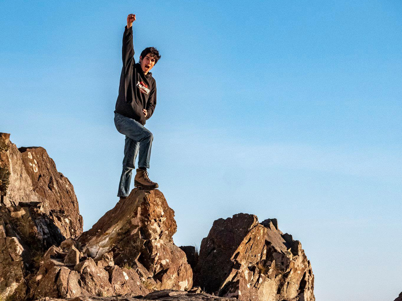 Young man standing atop mountain