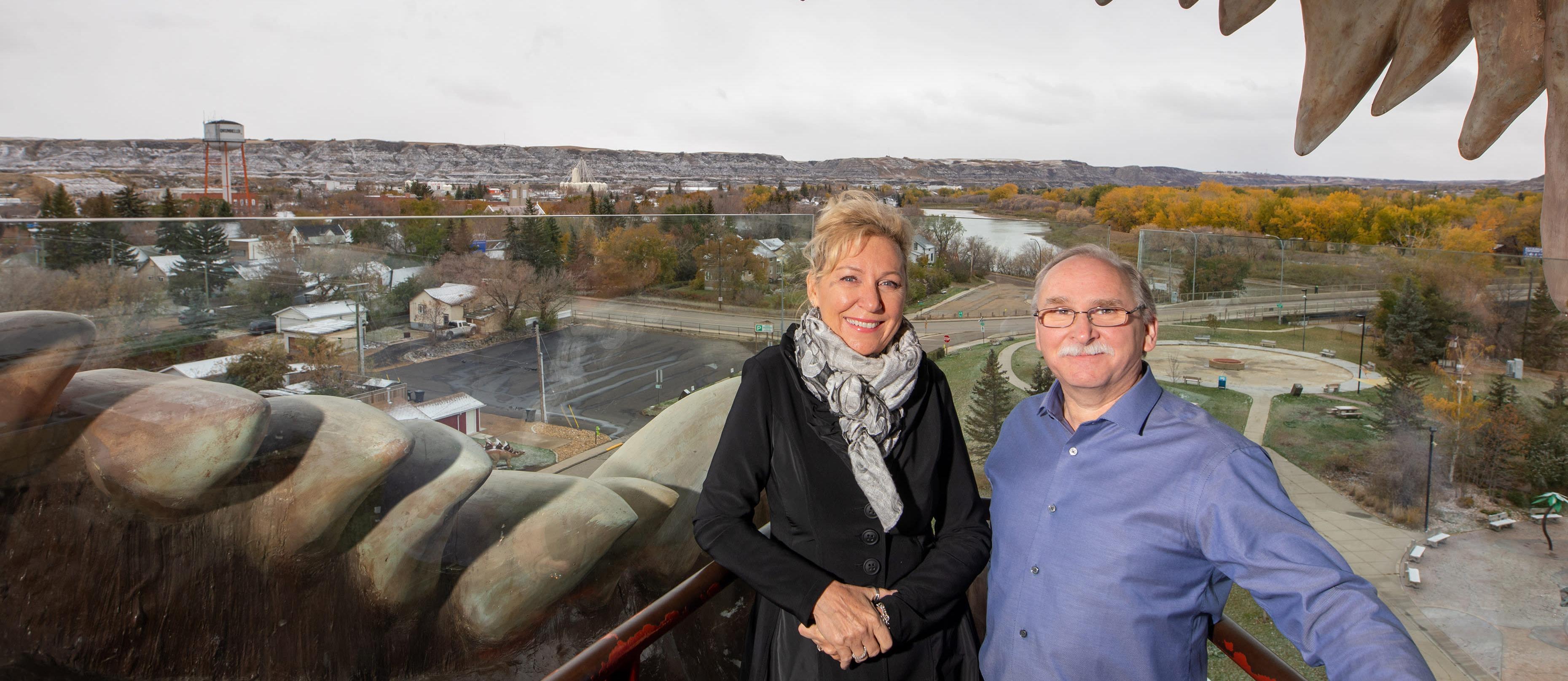 La mairesse de Drumheller, Heather Colberg, et l'entrepreneur local Brian Yanish sont debout dans la mâchoire d'une réplique de T-Rex.