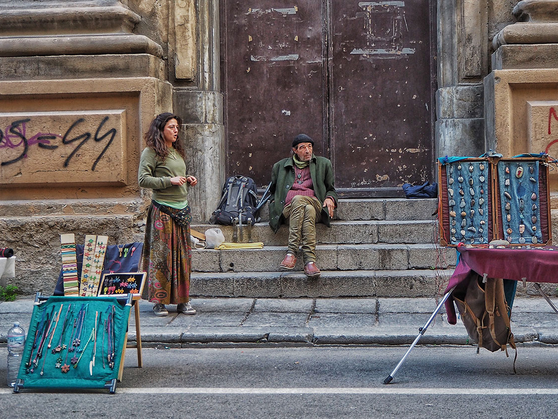 A pair of hawkers outside the steps of a church somewhere in Portugal