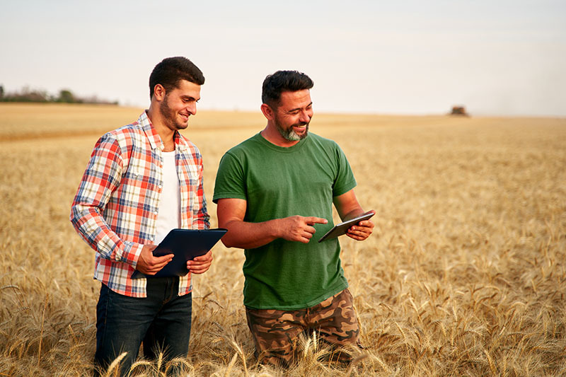 Two men standing in a field smiling and looking at an tablet.