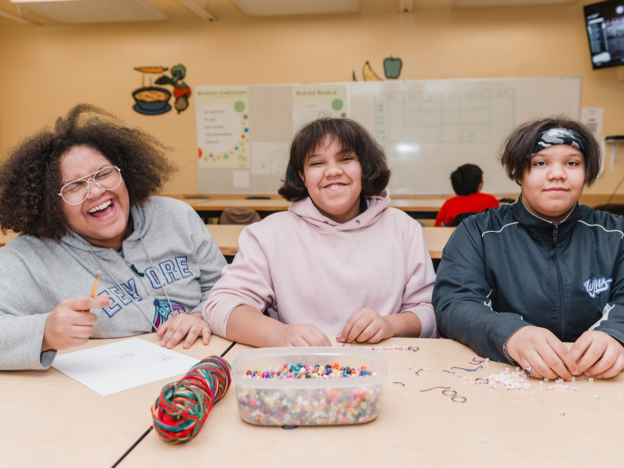 3 children sitting at a table laughing and smiling for the camera. The table in front of them has craft supplies like yarn and beads.