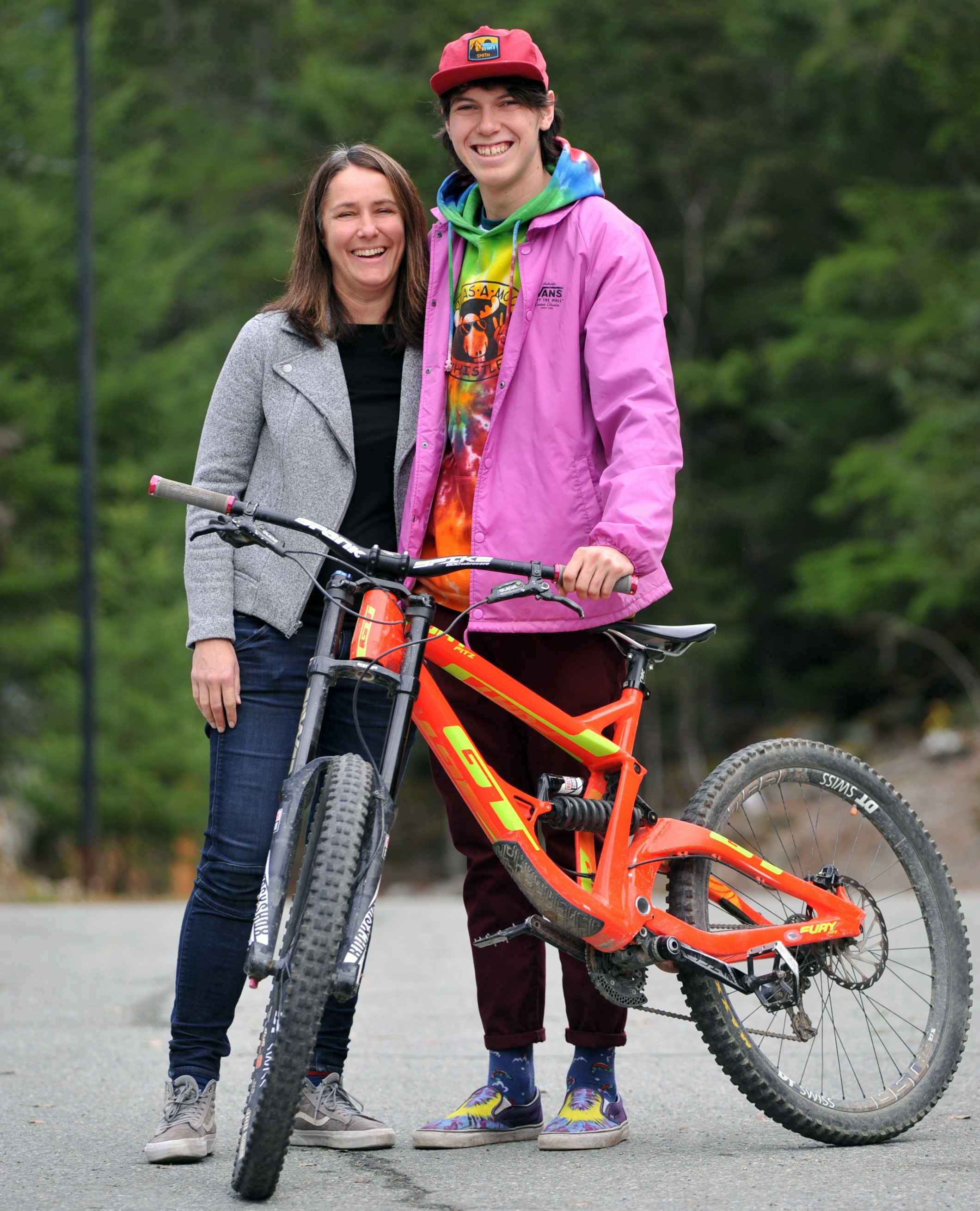 Dakota Williams with his mom, standing in front of a bicycle
