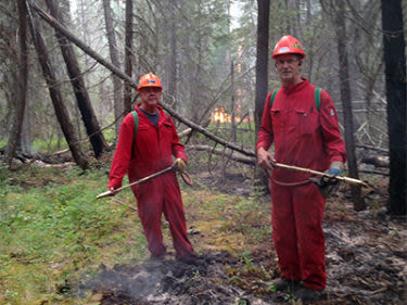 Two BC wildfire fighters in the forest