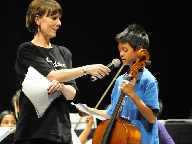 An OrKidstra participant and his instructor onstage