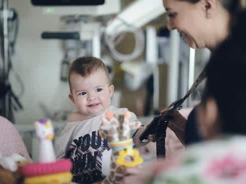 Baby playing with nurse's lanyard