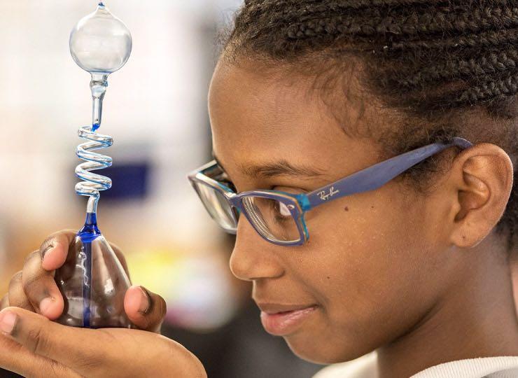 Young girl examining at lab beaker
