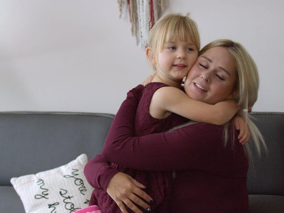 A mom hugging her daughter