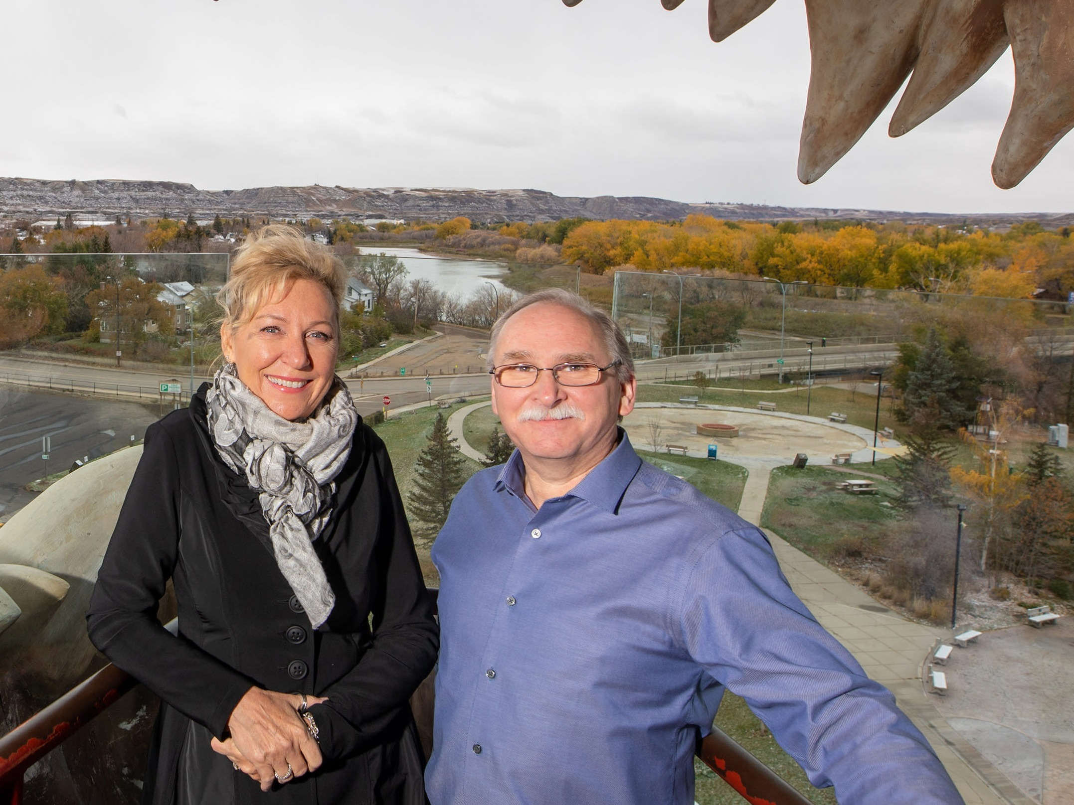 Drumheller Mayor Heather Colberg and local entrepreneur Brian Yanish stand in the mouth of a replica T-Rex.