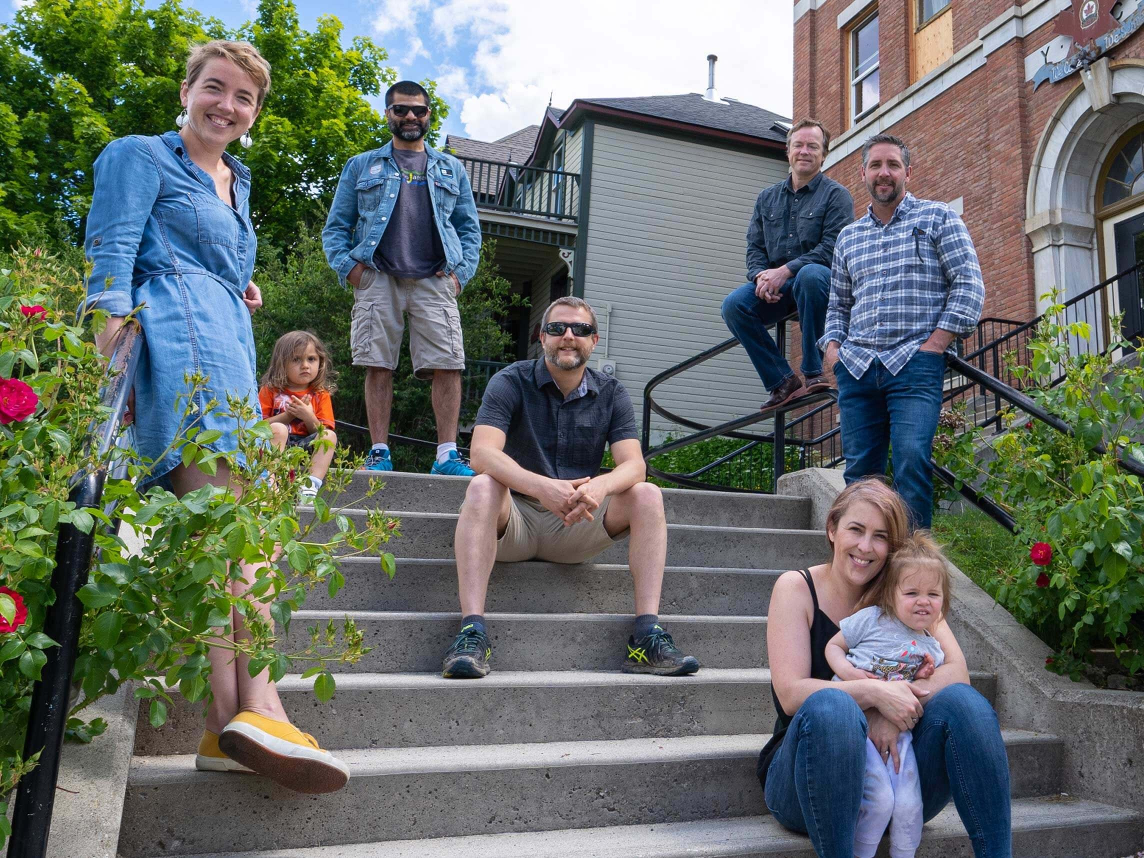 The Traction on Demand team sitting on the steps of their office in Nelson, BC.
