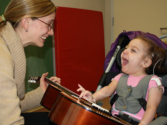 A music instructor engages with a laughing child