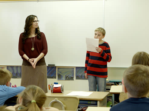 Conner making a presentation to his class as his teacher looks on