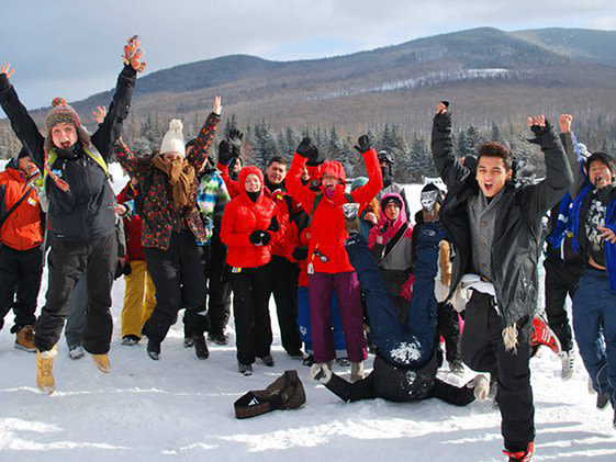 A group of cheering Motivaction Jeunesse youths standing on a snowy mountainside