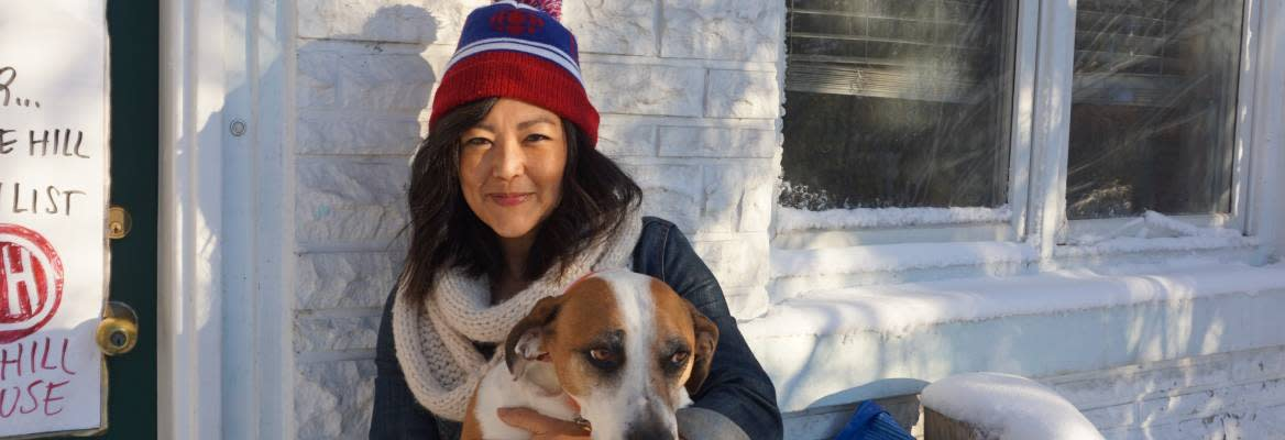 An Asian woman wearing a scarf and toque holding a brown and white dog
