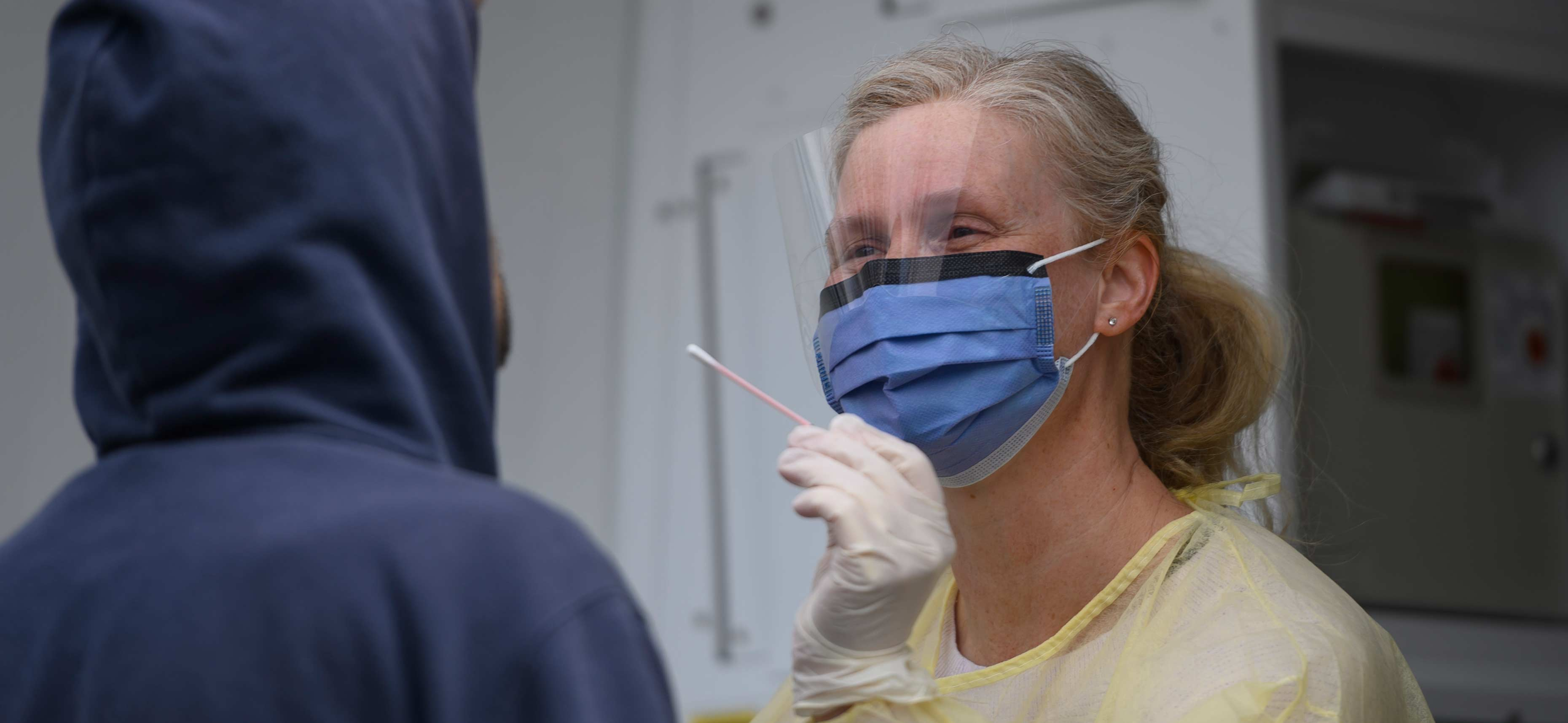 A nurse in personal protective gear administering a test.