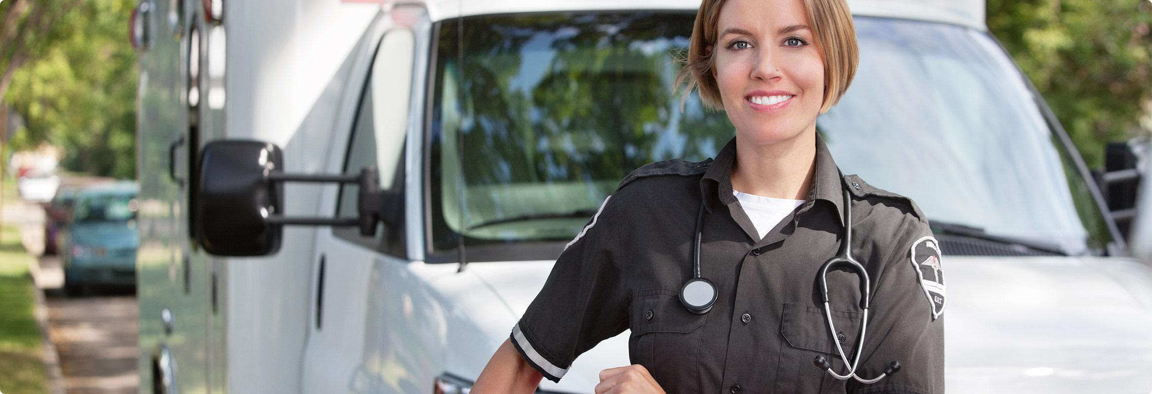 Une ambulancière devant son véhicule