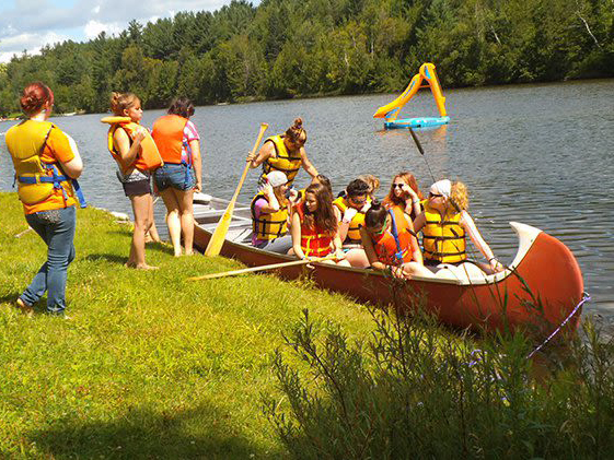 A group of camp kids boarding a large canoe