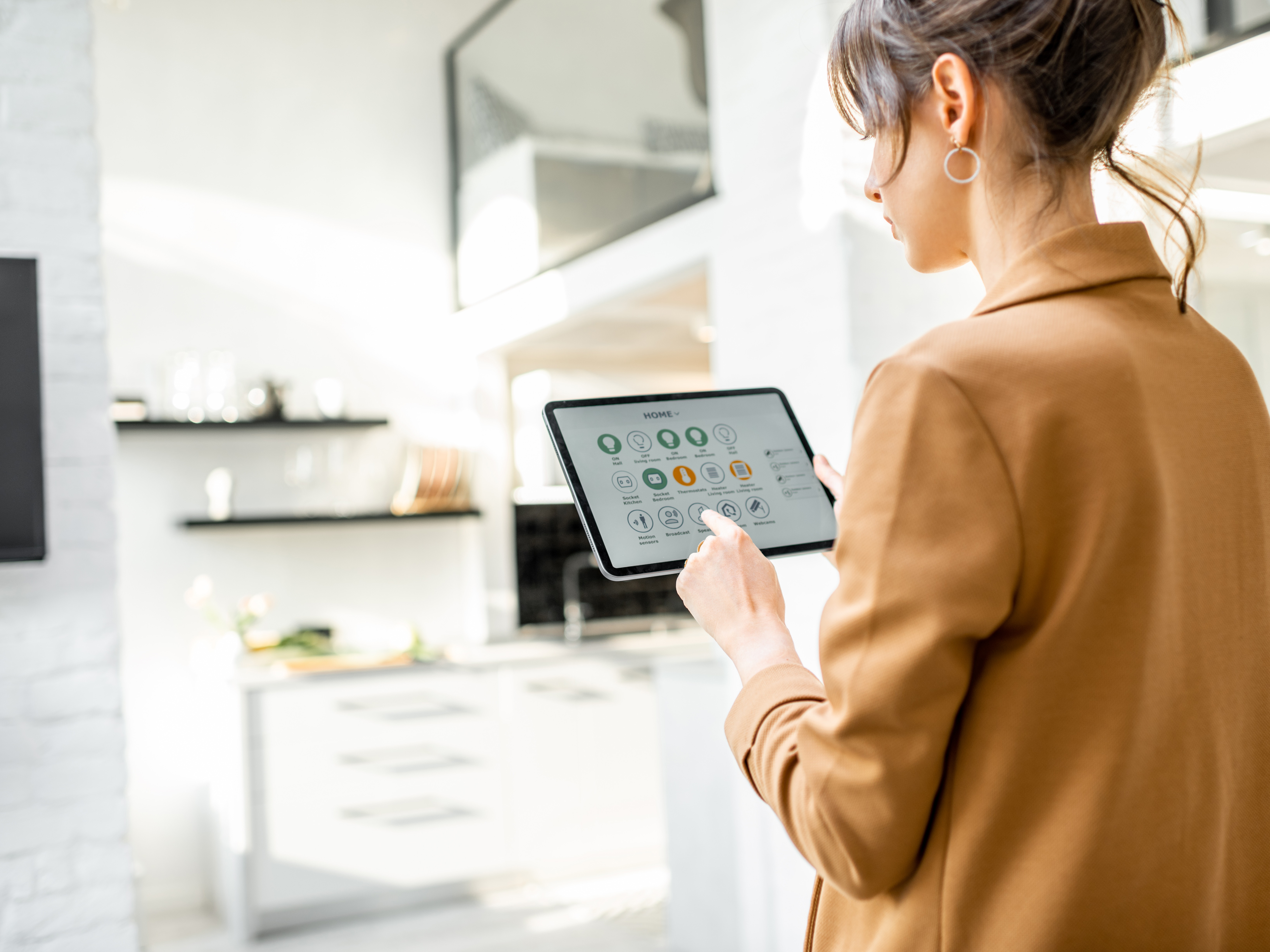 Woman standing in her home using an app on her tablet to operate home appliances