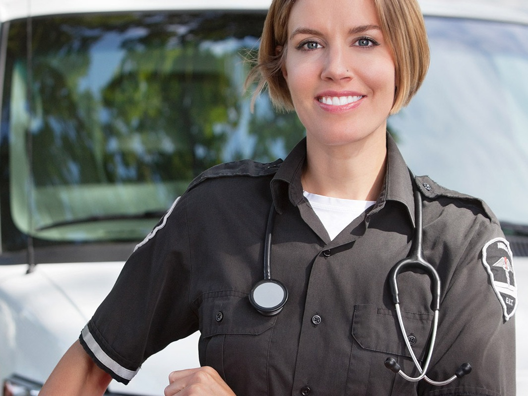 A female paramedic standing in front of her van