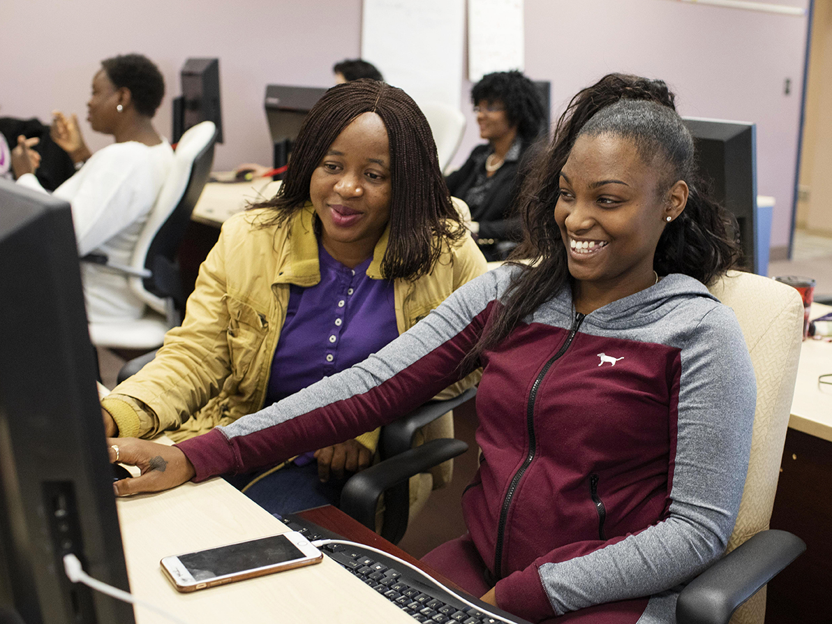 Two women working at a computer smiling