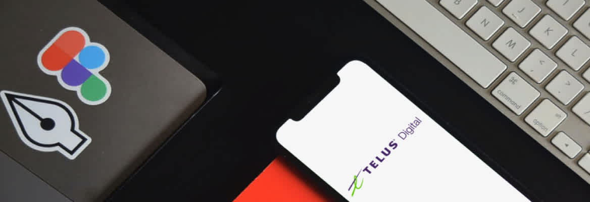 A mobile phone displaying the TELUS Digital logo next to a keyboard and laptop with stickers for NearForm and Figma