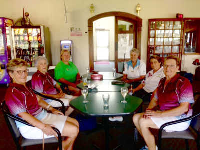 Harden Hawks in maroon uniforms towards front of table: L to R: Pat, Chris and Robyn and Cootamundra Mixed Girls at back of table- L to R- Donna, Karen and Jenny enjoying a drink after the game.