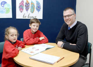 Ivy Cross and Ashley Walsh with Acting Principal Mr Graham Jones reading together to celebrate Book Week.