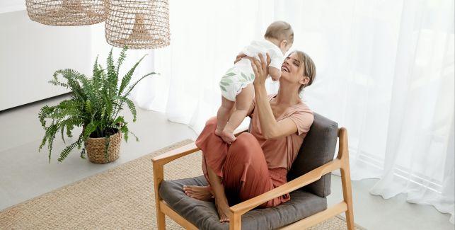 Mutter spielt mit ihrem Baby auf dem Schoß, im Hintergrund ist der Wickeltisch zu sehen.