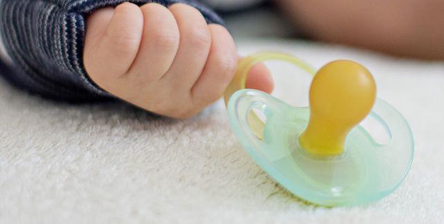 Babyhand neben der ein Schnuller liegt.