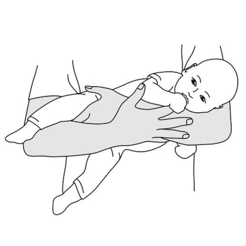 Ein Baby wird im Fliegergriff vor der Brust eines Elternteils gehalten.
