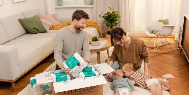 Eltern packen gemeinsam neben zwei Babys die Abo-Box aus