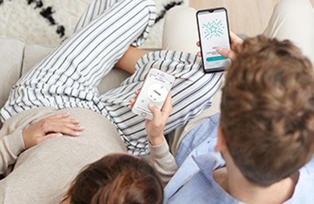 Eltern suchen gemeinsam auf dem Smartphone nach Namen