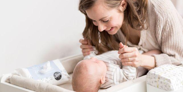 Mutter wickelt ihr Baby auf dem Wickeltisch