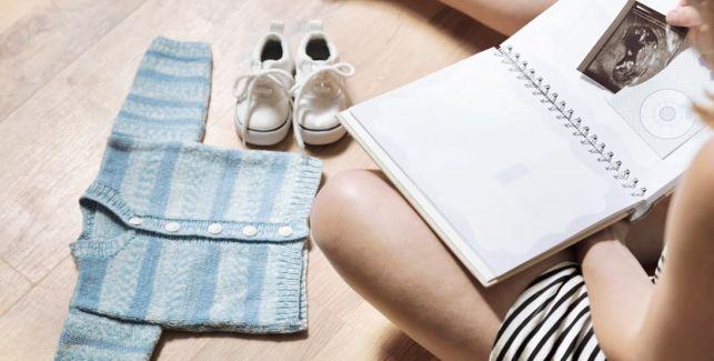 Kleinkind malt mit Fingerfarbe auf Bauch der schwangeren Mutter