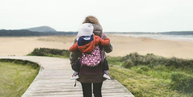 Mutter trägt ihr Baby in der Trage auf dem Rücken.