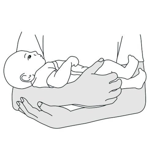 Ein Baby wird im Wiegegriff vor der Brust eines Elternteils gehalten.