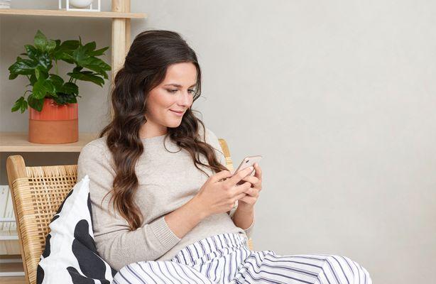 Schwangere Frau liest etwas am Smartphone