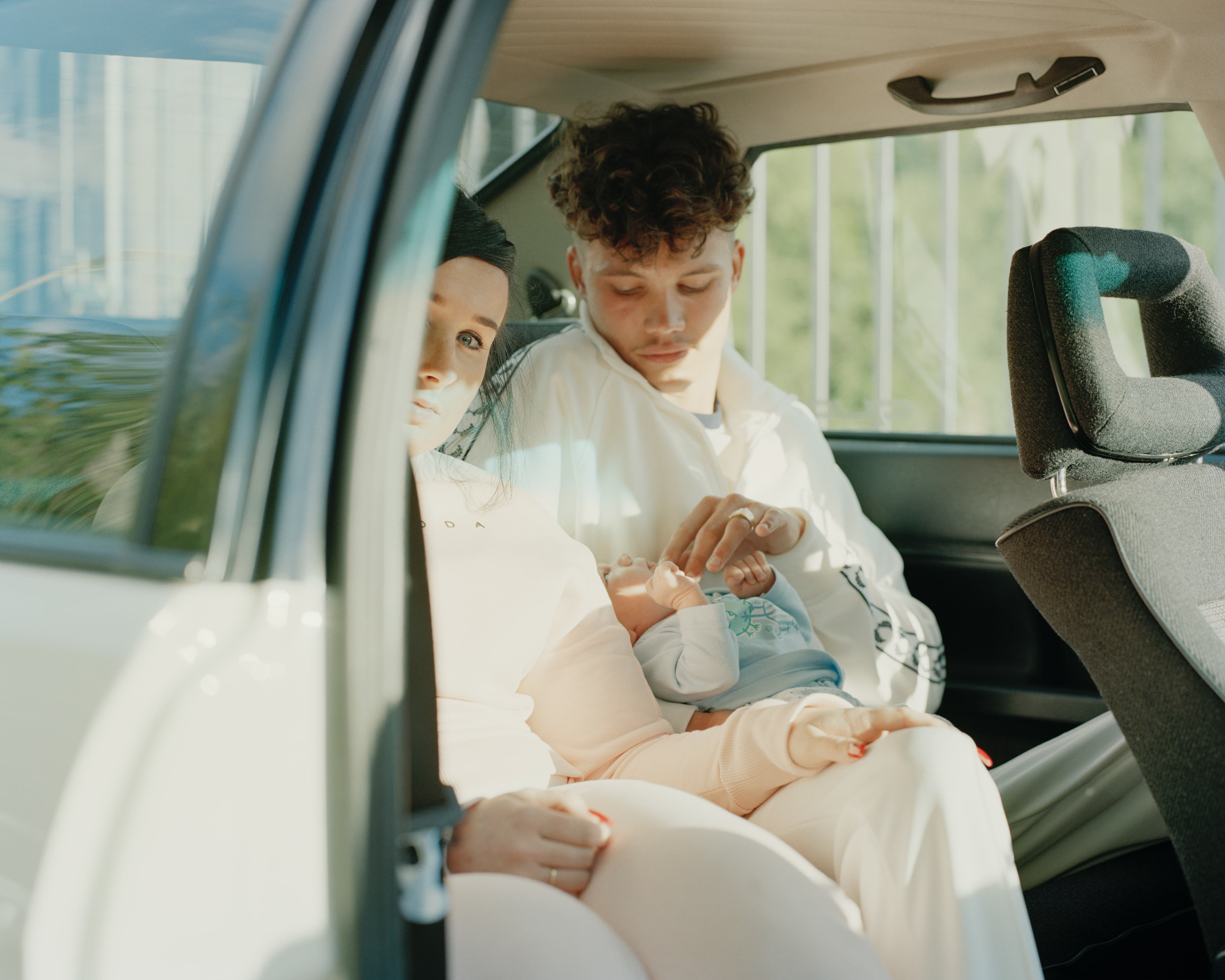 Couple in car holding baby