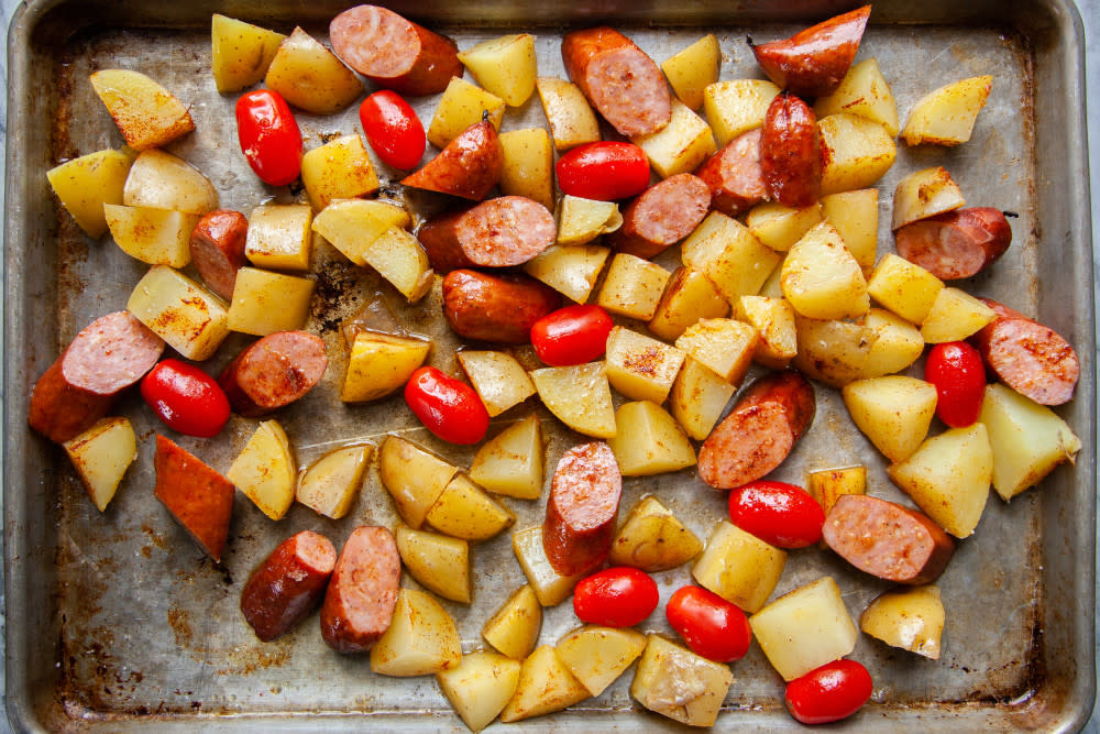 Place potatoes, sausage and tomatoes on sheet pan, drizzle with olive oil and season with salt, pepper, and paprika. Toss with your hands until everything is combined, then spread out on sheet pan in a single layer.
