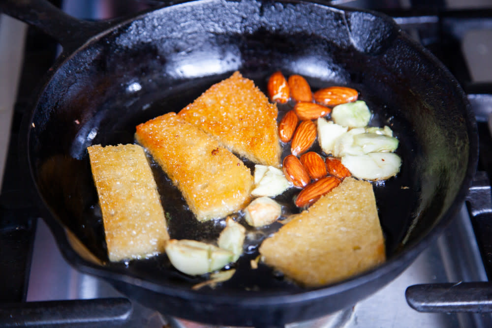 1. In a small skillet, heat 2 tablespoons olive oil over medium high heat. Add almonds, bread, and garlic and toast.