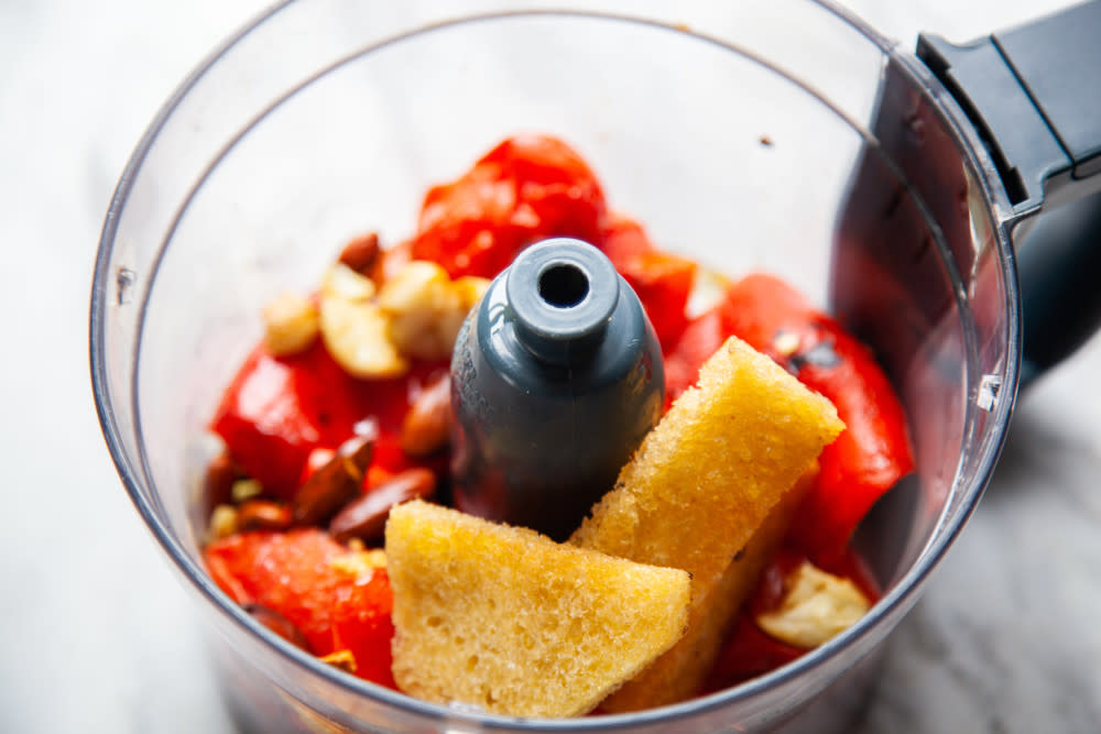 Place peepers, tomatoes, bread, garlic, vinegar, salt, paprika, and almonds in blender and pulse briefly.