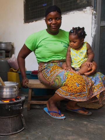Kochende Frau mit Kind in Ghana