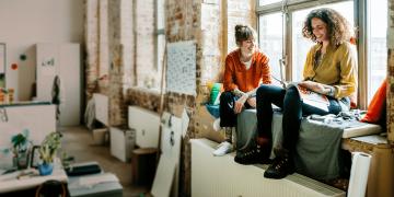 2 Frauen auf einer Heizung sitzend