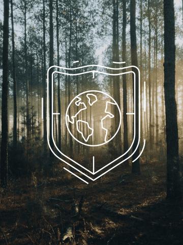 Schild mit Abbildung der Erde vor Waldkulisse